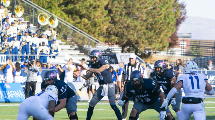 Quarterback Malik Henry, No. 16, drops back to pass in Mackay Stadium. Charging towards his are two San Jose State defenders while he is being guarded by two offensive linemen.