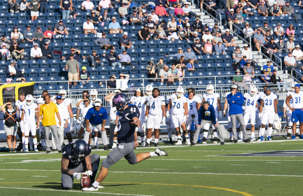 Brandon Talton plants his leg in the turf just before kicking a football. Talton is wearing a blue Nevada jersey with grey pants. His Nevada football helmet has pink cursive lettering that spells out 'Pack'