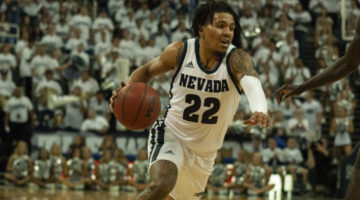 Jazz Johnson, wearing all white, dribbles a ball during a match in Lawlor Events Center.