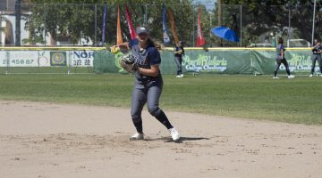 Charli McLendon warms up ahead of the Puerto Vallarta College Challenge. She is wearing a blue and grey softball uniform.