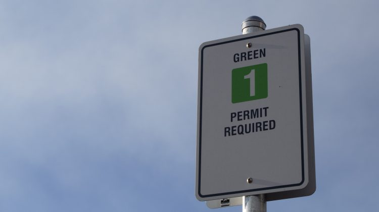 Sign for the green parking lot with sky behind it.